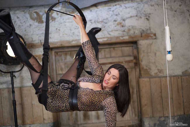 Leather boots seamed stockings Miss Hybrid rides the dungeon sex swing.